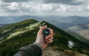 Hand holding compass overlooking mountains