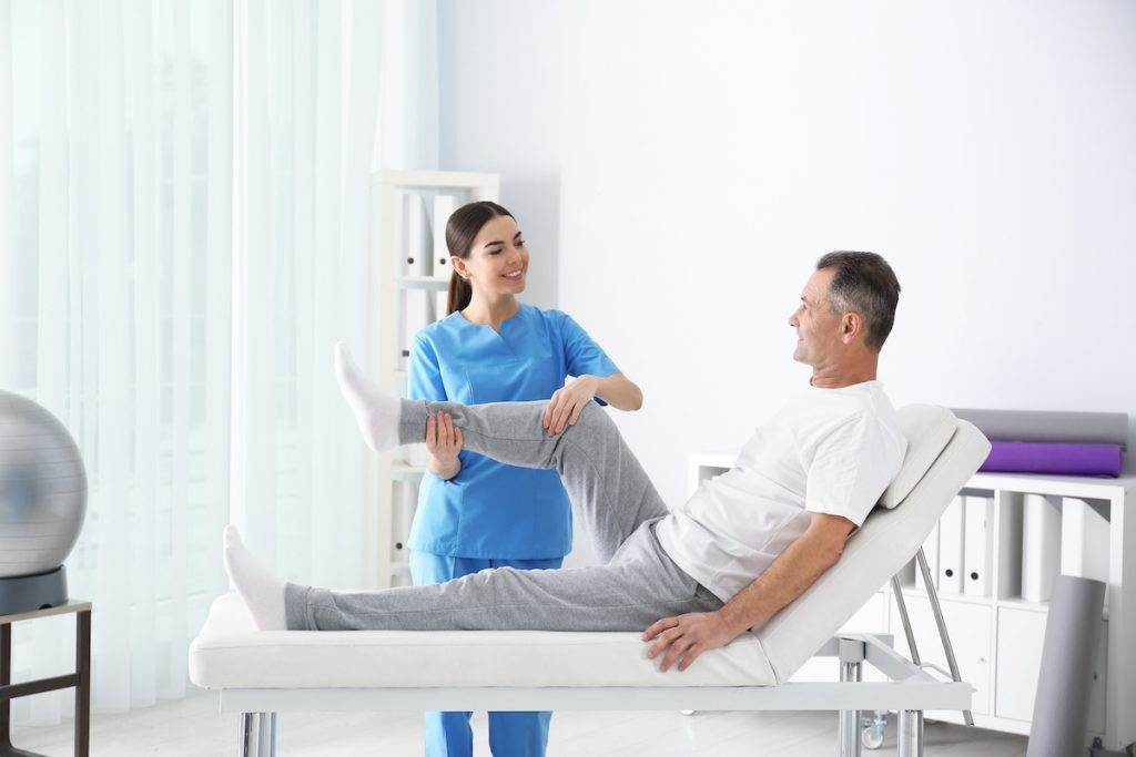 Female physiotherapist doing exercises with a patient after hip replacement surgery.