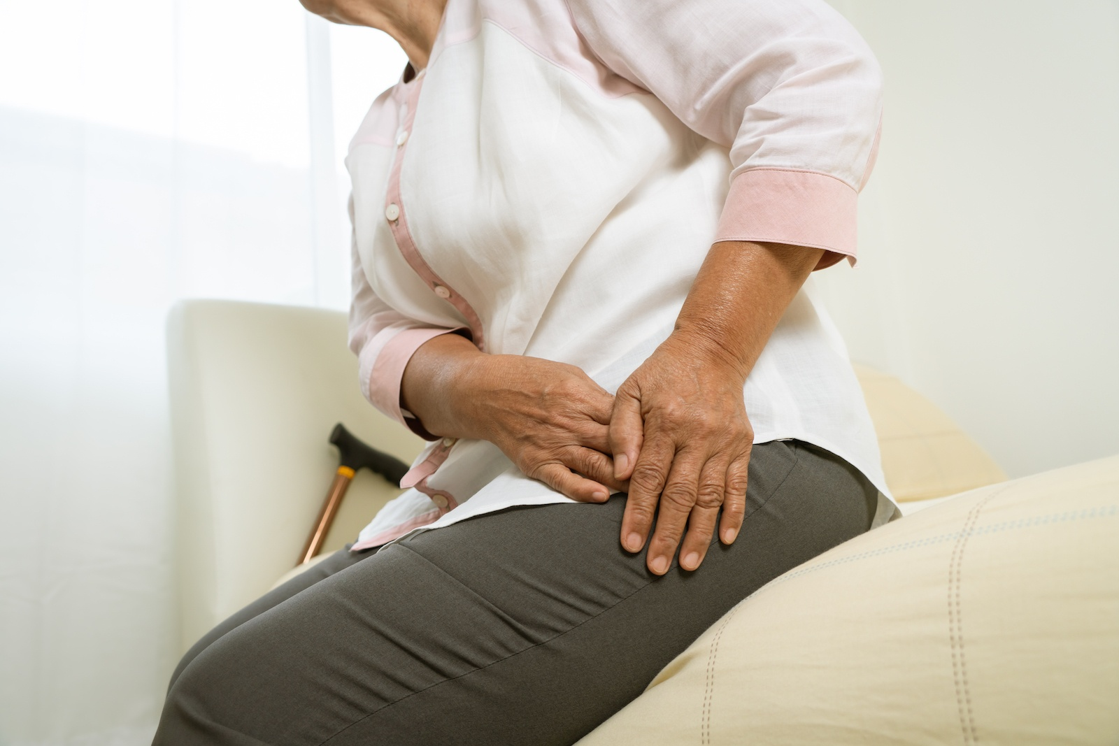 An older woman showing a sign of hip pain.