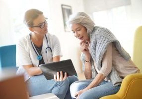 An older female patient asking a female doctor questions about hip replacement surgery